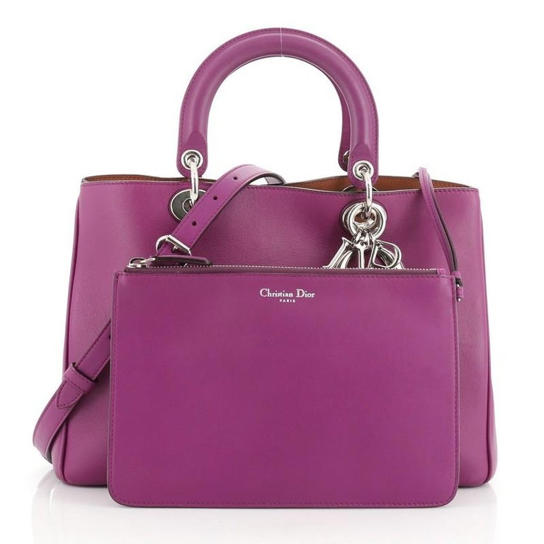 This Christian Dior Diorissimo Tote Pebbled Leather Medium, crafted from purple pebbled leather, features short dual handles with Dior charms, side snap buttons, protective base studs, and silver-tone hardware. Its magnetic snap button closure opens