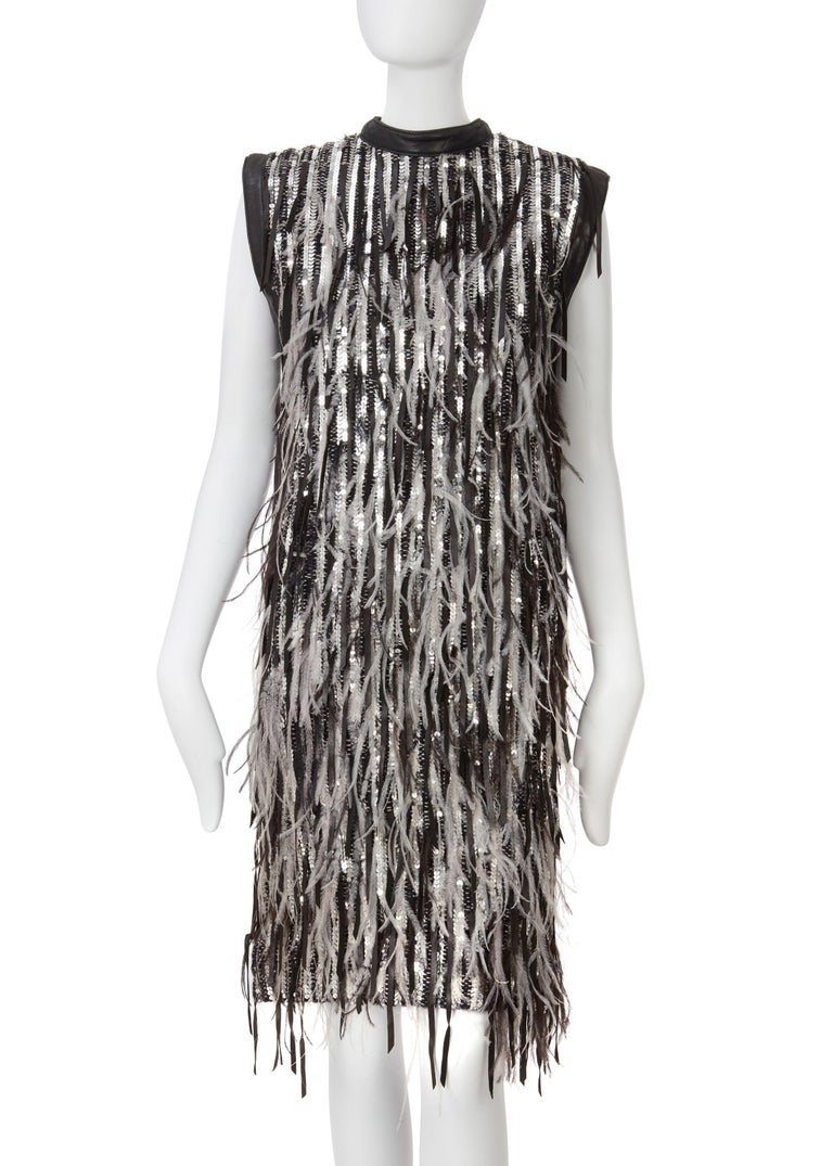 This is a Marc Bohan by Dior dress featuring high neck, feather, silver sequin and leather trim detail this dress is a perfect head-turning piece.