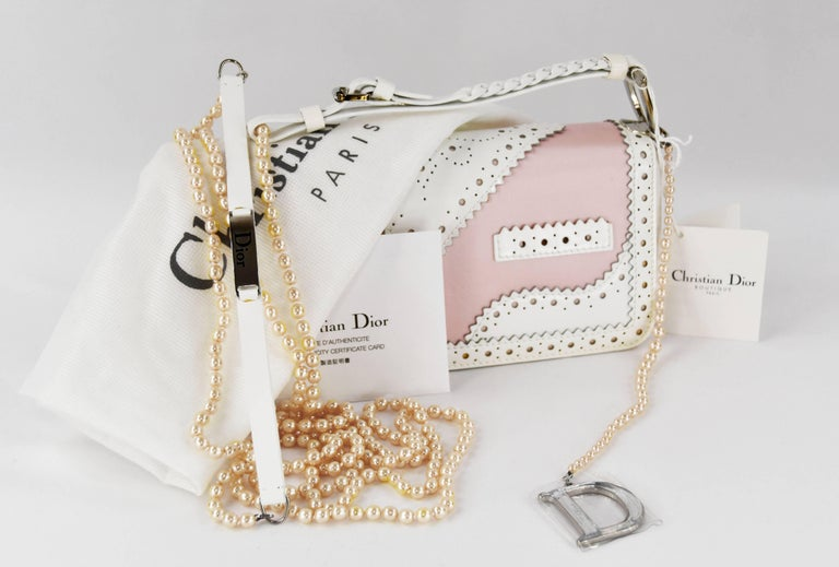 This is an exquisite Christian Dior patent D'Trick shoulder bag.  It is made out of pink and white leather that resembles the style of patent leather shoes with clutch handle with pearl necklace attached.  New with tags.  Bag measurements 8.5 inches