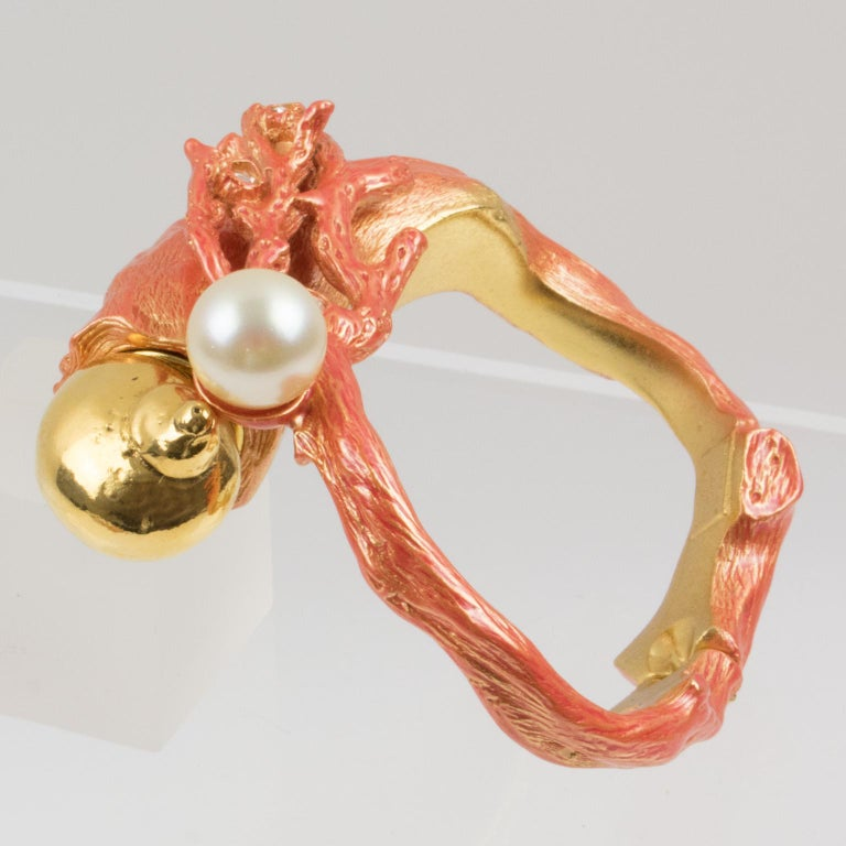 Stunning Christian Dior Paris signed clamper bracelet bangle designed for the launch of his Dune Fragrance in 1987. Sculptural coral branch dimensional design in gilt metal all textured with a bright orange enameling, topped with clear glass