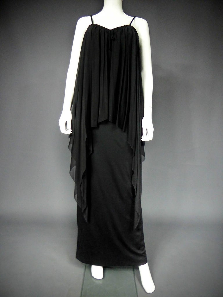 Circa 1975  France  Long bat dress in jersey and silk muslintightened at the chest by a tie. Sleeveless low-cut neckline retained by fine matching straps. Huge asymmetrical triangle with a pointed cut in bias and hands finishes. Cape effect