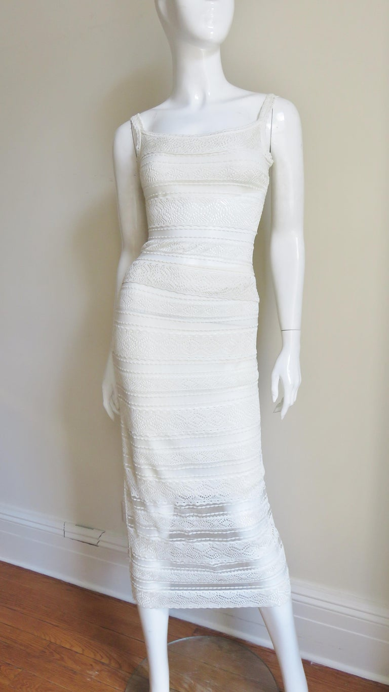 A fabulous 2 piece set in off white lace from Christian Dior.  It consists of a scoop neck camisole and straight midi length skirt in alternating lines of lace and sheer.  The camisole is lined through the bust and the skirt is lined to above the