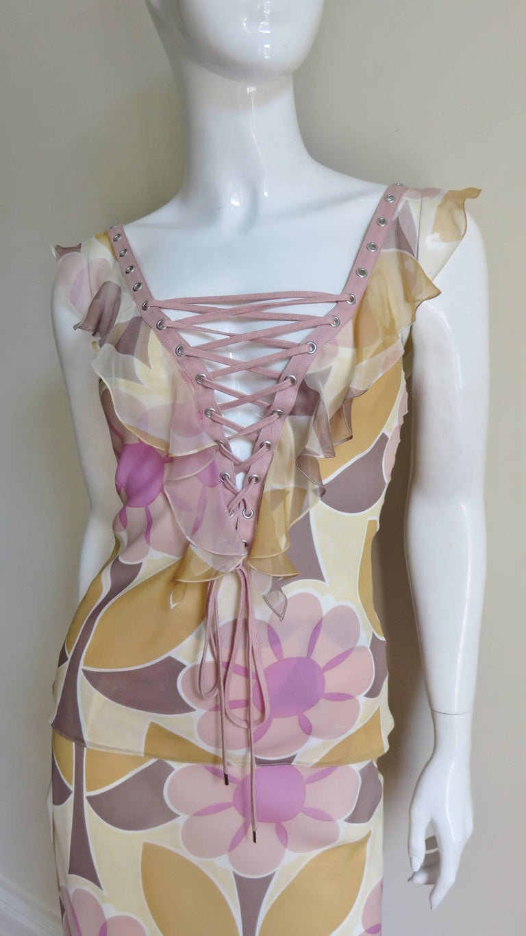 An incredible 2 piece set in a pink and yellow flower pattern silk from John Galliano for Christian Dior.  The top is fitted with adjustable functional pink lacing up the center front and back down to the waist with a delicate ruffle along it's edge