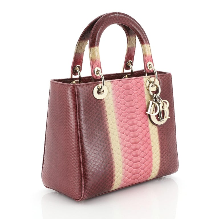 This Christian Dior Lady Dior Bag Python Medium, crafted in genuine purple multicolor python skin, features dual rolled handles with sleek Dior charms, and gold-tone hardware. Its top zipper closure opens to a purple leather interior with side zip