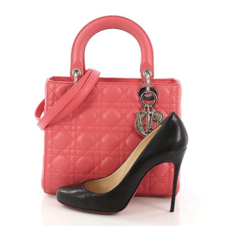 This Christian Dior Lady Dior Handbag Cannage Quilt Lambskin Medium, crafted in pink cannage quilt lambskin, features dual top leather handles, Dior charms, protective base studs, and silver-tone hardware. Its zip closure opens to a gray fabric