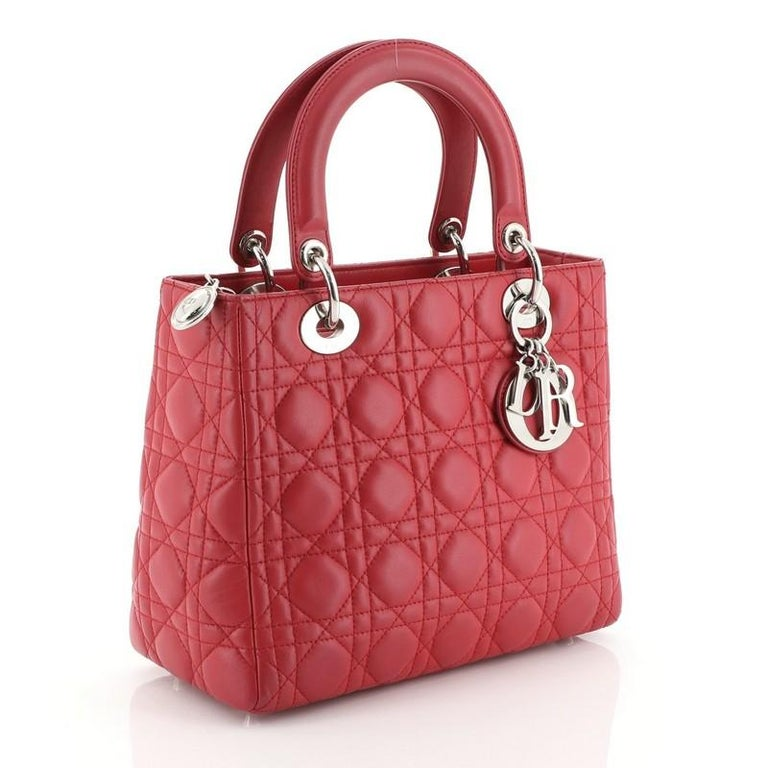 This Christian Dior Lady Dior Handbag Cannage Quilt Lambskin Medium, crafted in pink cannage quilted lambskin leather, features short dual handles with Dior charms and silver-tone hardware. Its top zip closure opens to a neutral fabric interior with