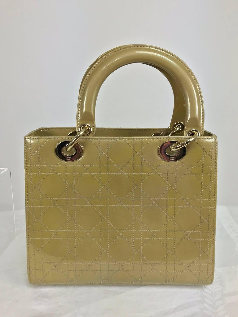 Christian Dior Lady Dior metallic golden patent leather handbag with pale gold hardware...Dior's iconic bag, the Lady Dior, features all the hallmarks of Dior leather goods: patent leather top stitched with the iconic Cannage motif, rounded handles