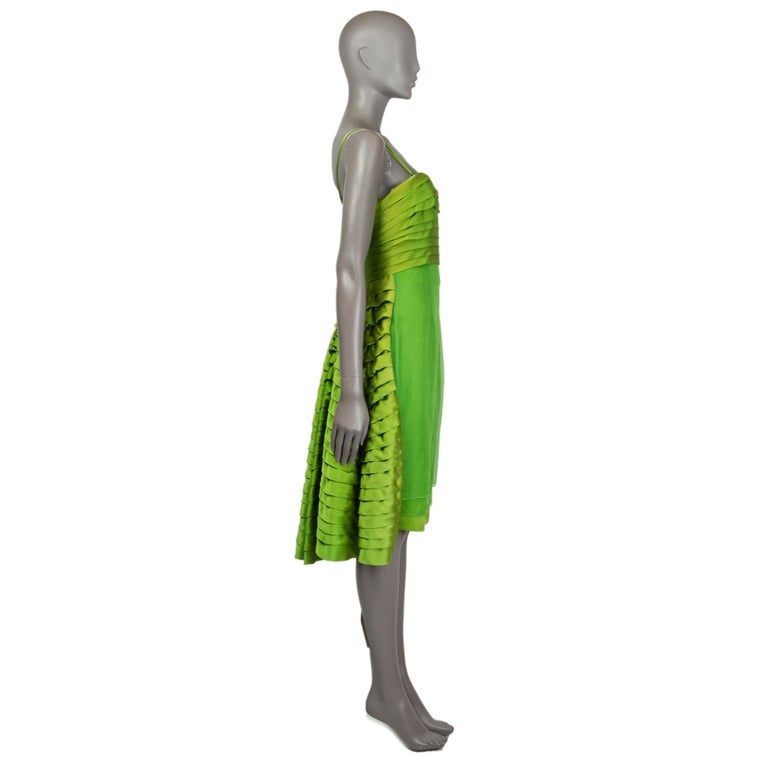 Christian Dior dress in chartreuse silk organza and satin (100%). With phorizontal pleating around the bust, wired bustier, ruffled panel on the back side, and layered skirt. Features removable shoulder straps. Closes with invisible zipper on the