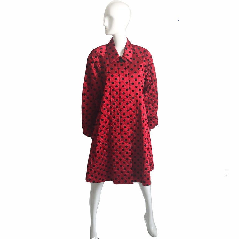 This fabulous evening coat was made by Christian Dior, most likely in the early 80s.  Made from silk satin, it features a black polka dot motif, dolman sleeves and a wide swing hem.  Fully lined with shoulder pads and fastens with one button at the