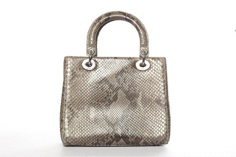 Dior grey Lady Dior bag with gold-tone hardware, optional flat leather shoulder strap featuring customizable charms, dual flat top handles, protective feet at bottom, tonal jaquard lining, single zip pocket at interior wall and zip closure at
