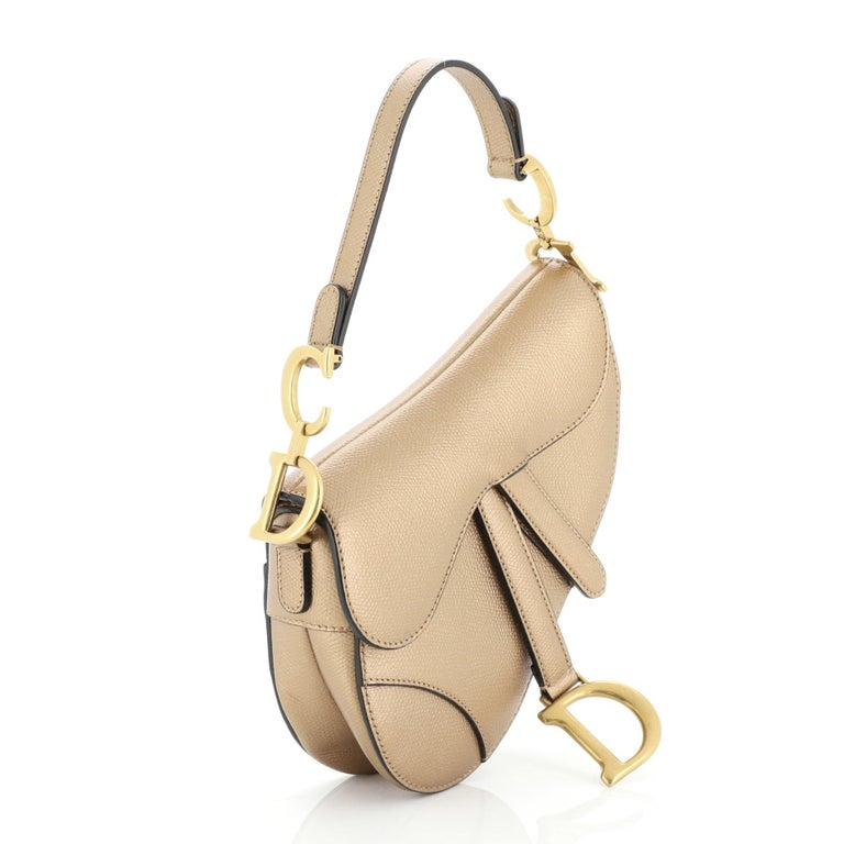 This Christian Dior Saddle Handbag Leather Mini, crafted from metallic leather, features a top handle adorned with metal 'CD' hardware and gold-tone hardware. Its fold over top opens to a neutral suede interior with zip pocket.   Condition: