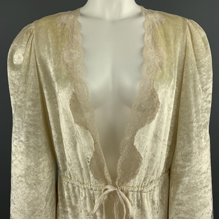 Vintage CHRISTIAN DIOR LINGERIE for I.MAGNIN robe top comes in cream crushed velvet with a deep V neck, drawstring waist tie closure, and beige lace trim.   Very Good Pre-Owned Condition. Marked:  Measurements:  Shoulder: 15 in. Bust: 40 in. Sleeve: