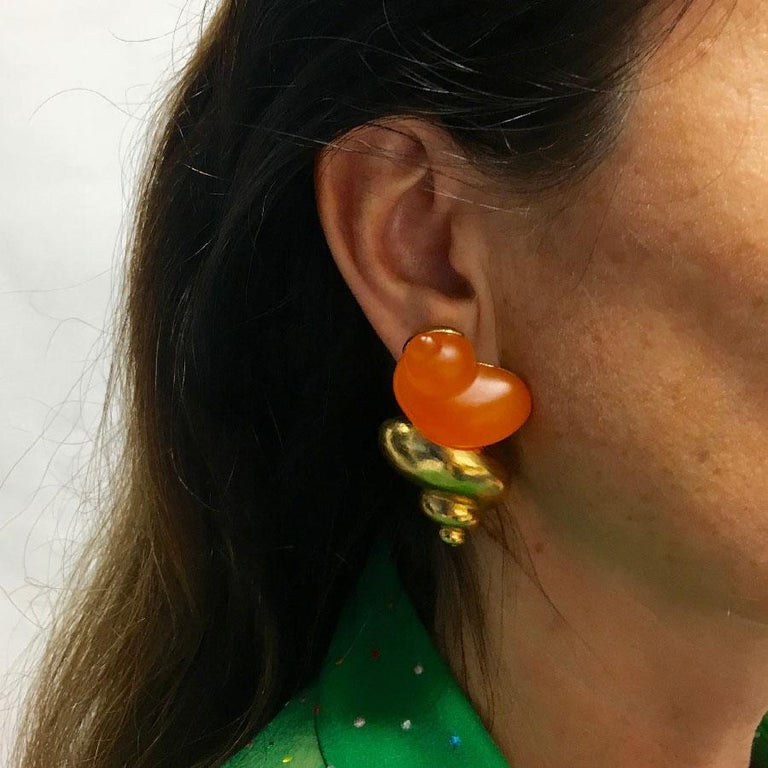 Ear clips in the shape of golden metal snails and orange resin. Perfect condition. Made by Robert Goossens, for the launch of a perfume. Length: 5.5 cm, width: 3 cm.  Very good condition. Delivered in a non original pouch.
