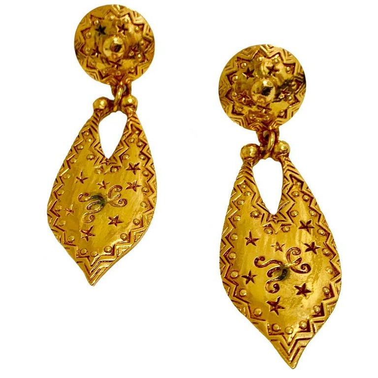 Find here a pair of hammered golden metal clip earrings, with stars and various engraved patterns. They have a real vintage look from the 90s that we love. The earrings are in good condition. We can however see on the photos, a little black in the