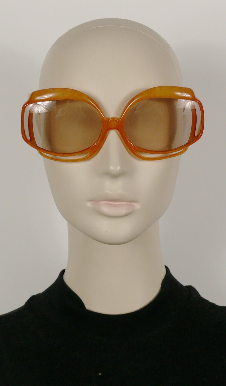 **** WE NO LONGER SHIP SUNGLASSES TO THE USA ****  CHRISTIAN DIOR vintage oversized sunglasses featuring a tangerine colour marbled frame, tinted plastic lenses and silver toned detailing.   Marked CHRISTIAN DIOR. OPTYL Made in