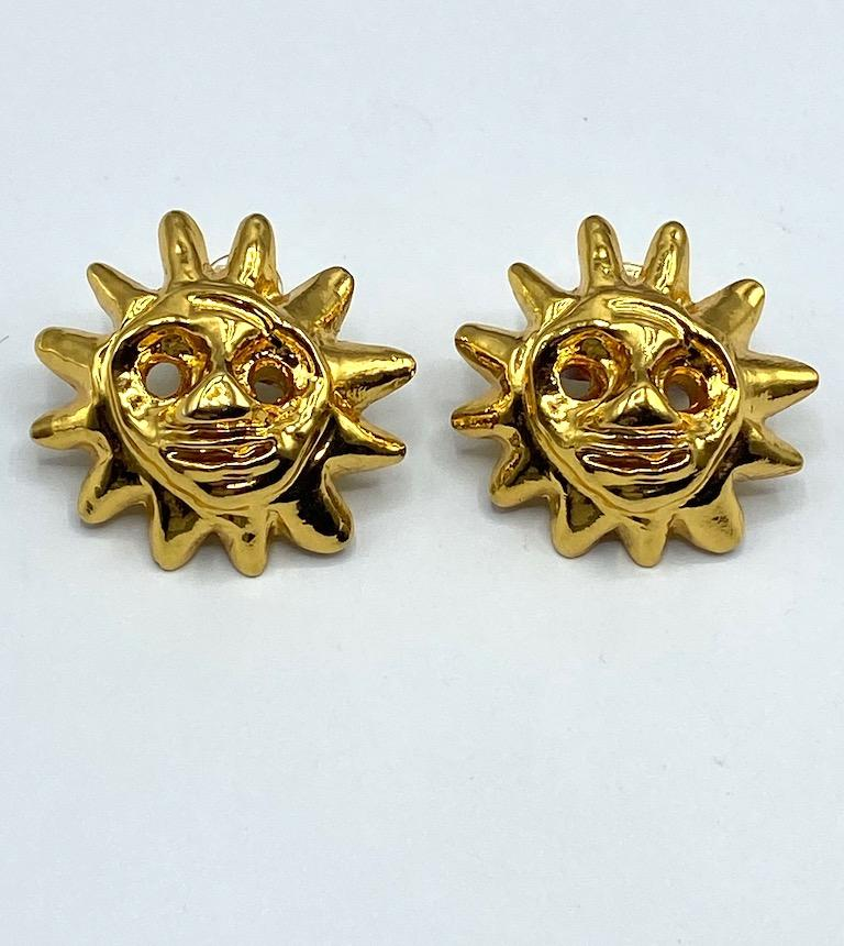 A beautiful and iconic pair of 1990s Christian Lacroix smiling sun face earrings. The sun face is one of Lacroix's favorite motifs. Each earrings measures a large 1.75 inches in diameter and .63 of an inch deep not including the clip back. The
