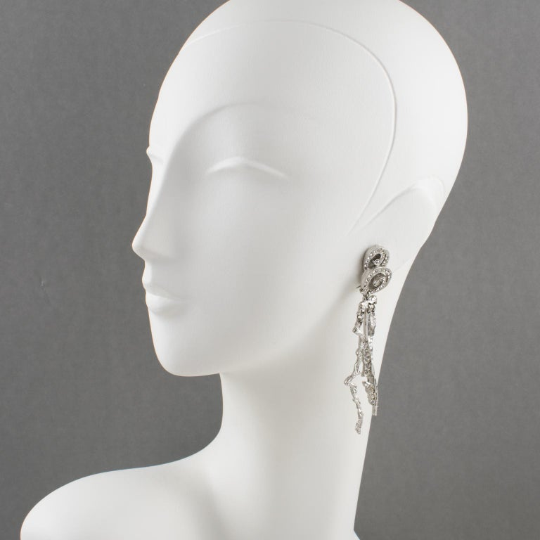 Superb Christian Lacroix Paris futurist clip-on earrings. Featuring a long dimensional brutalist dangling shape, with silvered metal all carved and see-thru, compliment with crystal rhinestones. Engraved