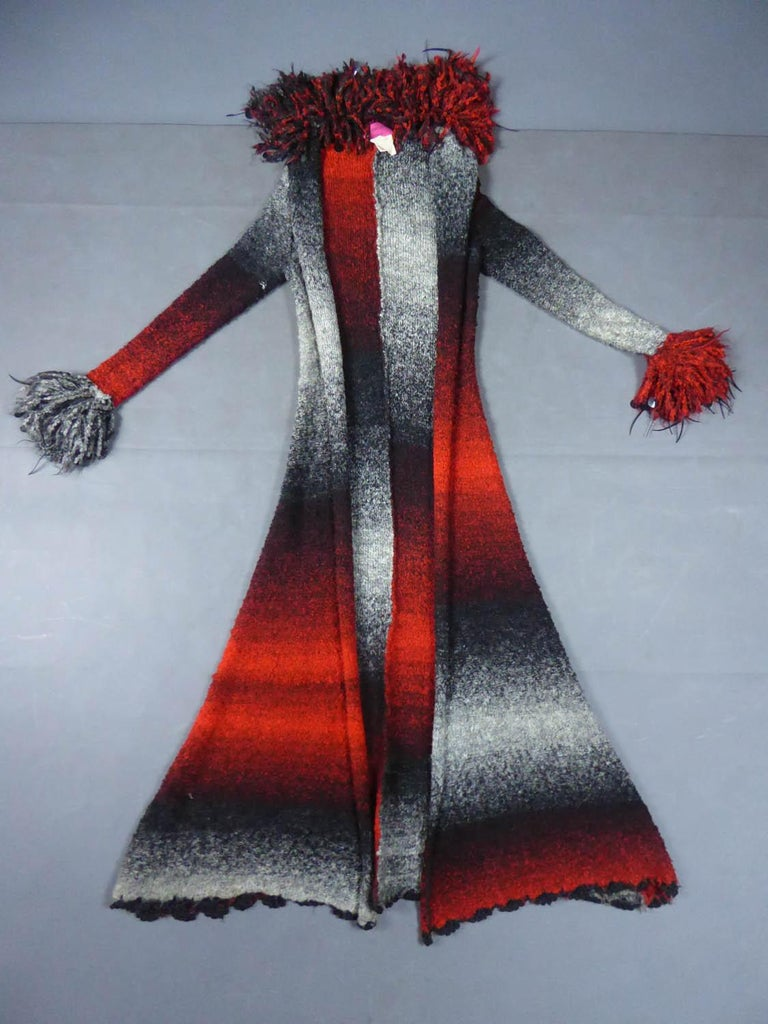 Circa 1985 France  Long eccentric coat in chiné knitted wool with a gradiation from gray to red from the designer house Christian Lacroix and dating from 1985. Exrtravagants wrists and collar in chiné bouillonné wool embroidered with sequins and