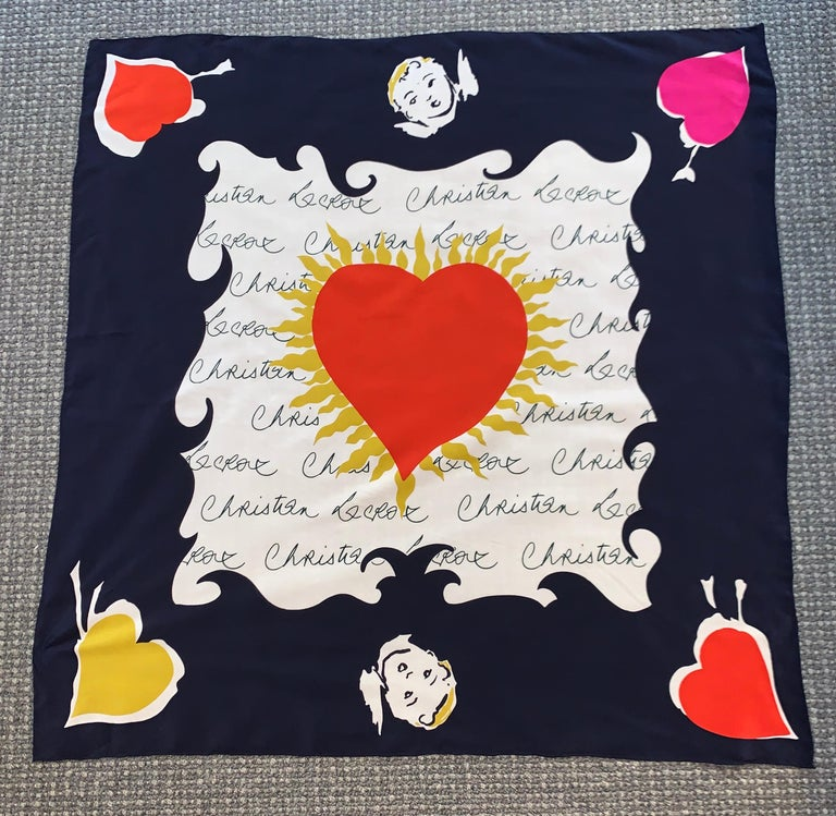 Christian Lacroix silk scarf with black and white signature print featuring cupids and hearts in red, yellow, and pink. Hand rolled edges.  100% silk.  Made in Italy.  Measures approximately 34