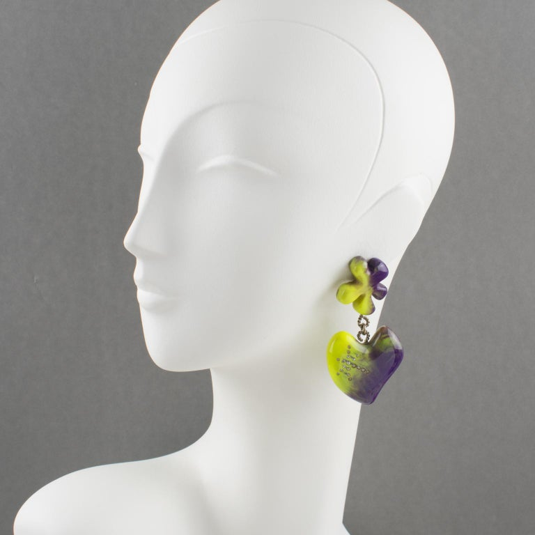 Stunning Christian Lacroix Paris signed clip-on earrings. Oversized bright colors resin dangling shape, featuring abstract flower and heart ornate with clear crystal rhinestones. Fabulous amethyst purple with pistachio green color, all marbled and