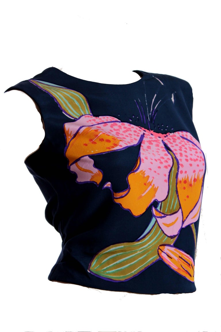 This stunning silk blouse was made by Christian Lacroix for his haute couture collection, most likely in the early 1990s.  Made from crisp navy silk, it features a bold hand-painted lily in front, pleating detail at the sides and fastens in back