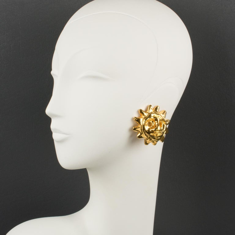 Stunning Christian Lacroix Paris signed clip-on earrings. Featuring dimensional gilt-metal coated resin sun mask with a high shine finish aspect. Marked underside: