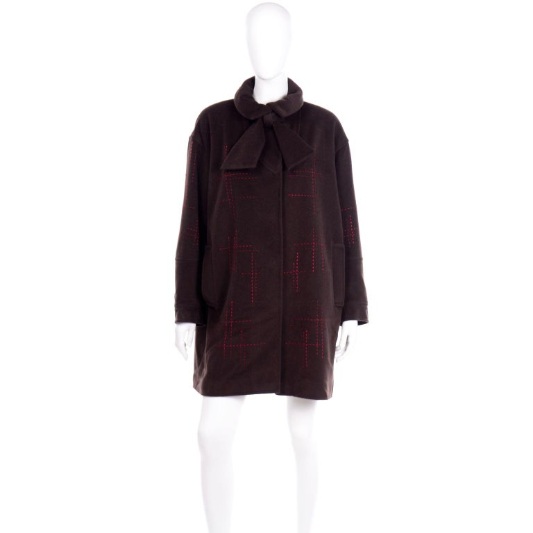 This vintage 1980's brown Christian Lacroix coat has unique red topstitching in a cross-hatch pattern throughout the silhouette. The folded, pointed collar of this jacket has darts and a fabric tie that can be tied in a knot or a bow. This cozy,