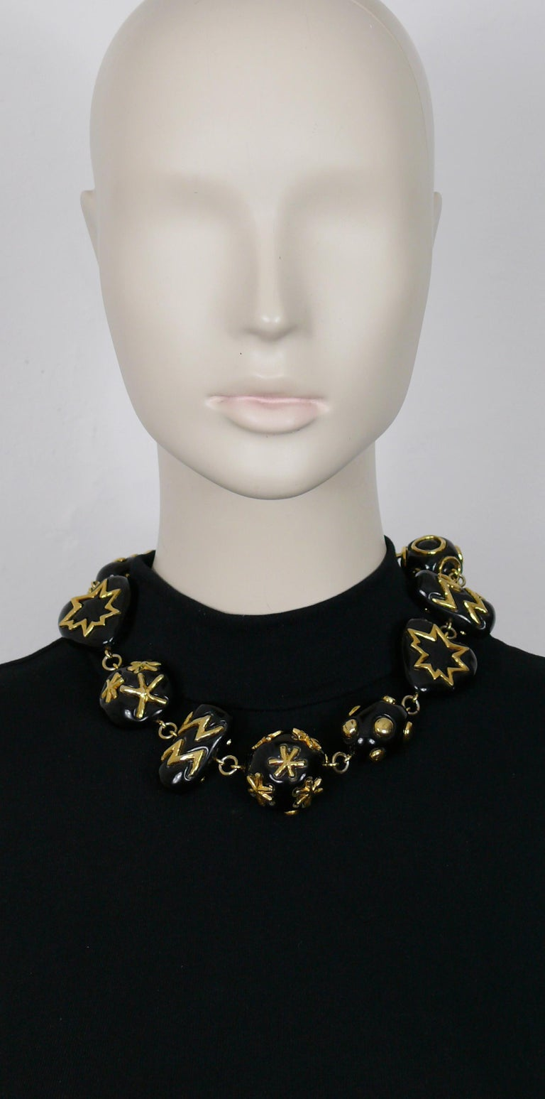 CHRISTIAN LACROIX vintage necklace featuring large black resin links of various shapes (rectangular, hearts, pebble, balls) with gold toned embellishement.  T-bar and toggle closure.  Marked CHRISTIAN LACROIX CL Made in France.  Indicative