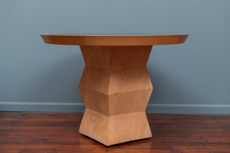 Christian Liaigre design Yquem pedestal table in solid oak with adapted black granite and oak top. Small wood chip on pedestal base corner.