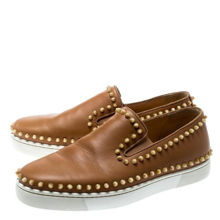 Add a unique style statement to your look with these eye-catching and fashionable Christian Louboutin Pik Boat slip-on sneakers. Constructed in beige leather, these shoes feature chunky rubber soles and spikes on the exterior.  Includes: Original