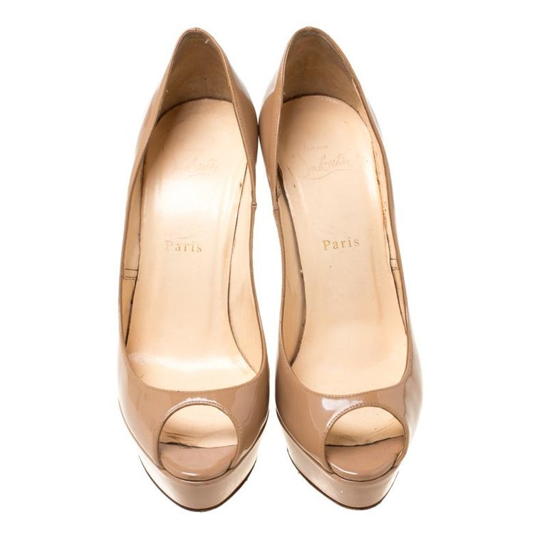 Stand out from a crowd with this gorgeous pair of Louboutins that exude high fashion with class! Crafted from patent leather, this is a creation from their Lady Peep collection. They feature a classic beige shade with peep toes and a glossy