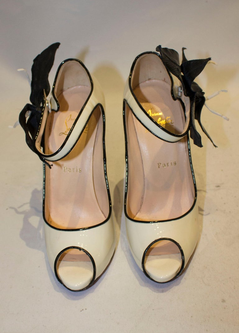 A fun pair of shoes by Christian Louboutin,in patent cream leather with a black trim. The shoes have a peep toe, hidden platform, and ankle strap with popper detail and flower decoration. Size 38 , heel height 5''.
