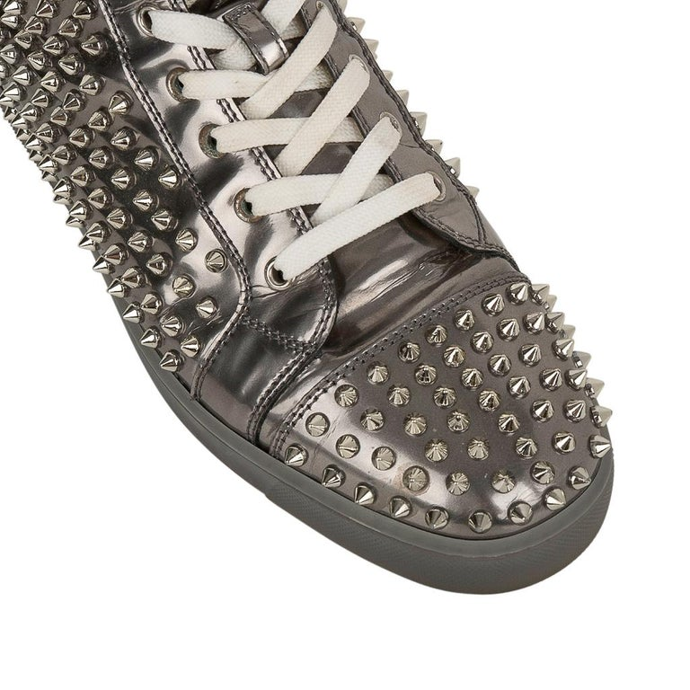 Guaranteed authentic  Christian Louboutin mens Louis Flat Antispecchio high top sneakers.   Patent leather silver gray high top sneaker with signature silver spikes. Logo plaque on side of shoe. Very minimal show of wear.  Comes with signature box