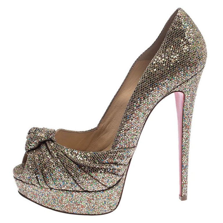 How gorgeous are these pumps from Christian Louboutin! They've been beautifully covered in glitter fabric and styled in a gathered knot on the uppers. These pumps carry peep-toes, platforms with 15.5 cm heels, and the signature red soles. Let this