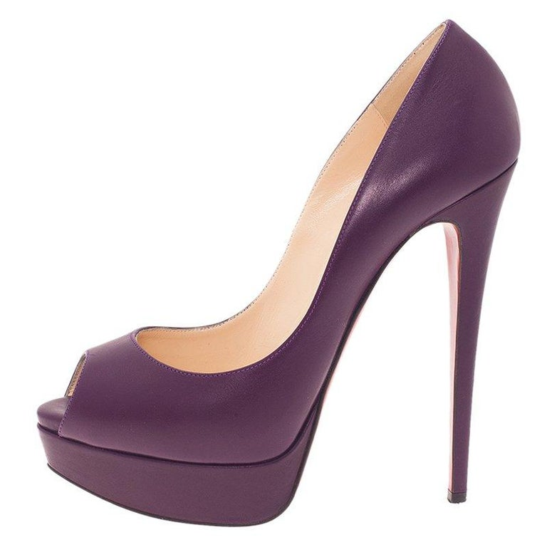 These Christian Louboutin pumps are a classic pair of shoes for any lady. They feature purple leather uppers, peep toe, self covered platforms, and 15.5 cm high heels. These pumps are lined with beige leather and have Christian Louboutin labeled