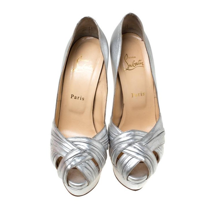 These classic pumps from the house of Christian Louboutin is that versatile pair that you can wear with many of your outfits. It features a silver leather body with crisscross straps on the front, set on a low platform sole and comes with a
