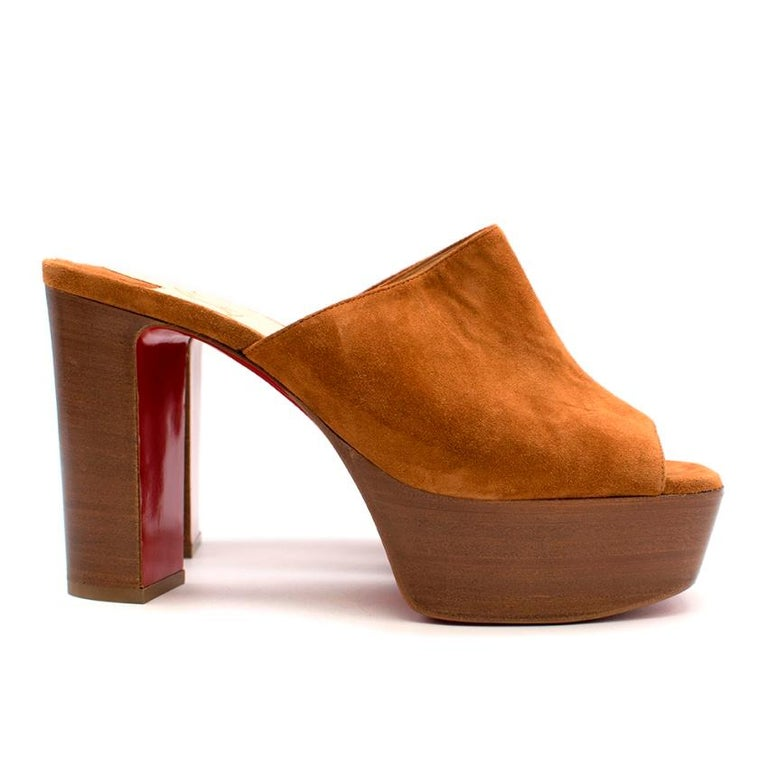 Christian Louboutin 100 suede platform mules  Christian Louboutin's peep-toe mules are designed in a warm hue that will compliment almost anything in your wardrobe. This pair is set on a chunky heel with a 40mm platform and features the label's