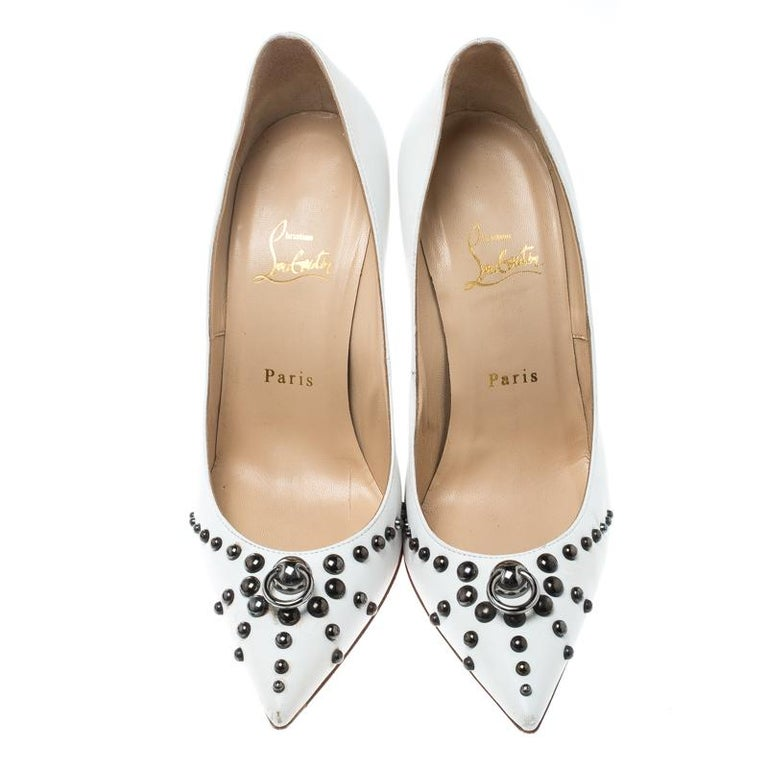Glamour is personified by these Christian Louboutin pumps. Crafted in leather, these pumps in white are accented with black-tone hardware. They feature pointed toes, metallic studs on toe caps and vamps, and a mock door-knock detailing on the vamps.