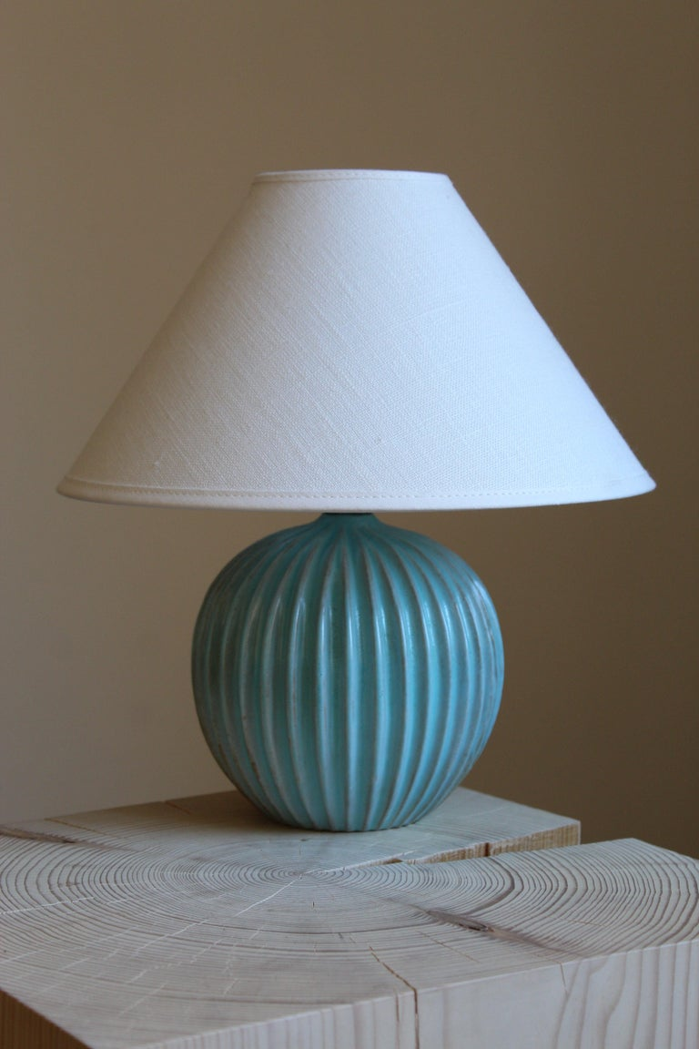 A table lamp produced by Christian Schollert. In blue-glazed stoneware. Produced in Denmark, 1960s. Signed. Brand new linen lampshade.