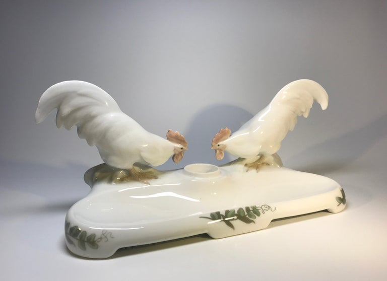 Designed by Christian Thomsen of Royal Copenhagen, Denmark, this fine antique porcelain inkstand features two white cocks feeding.