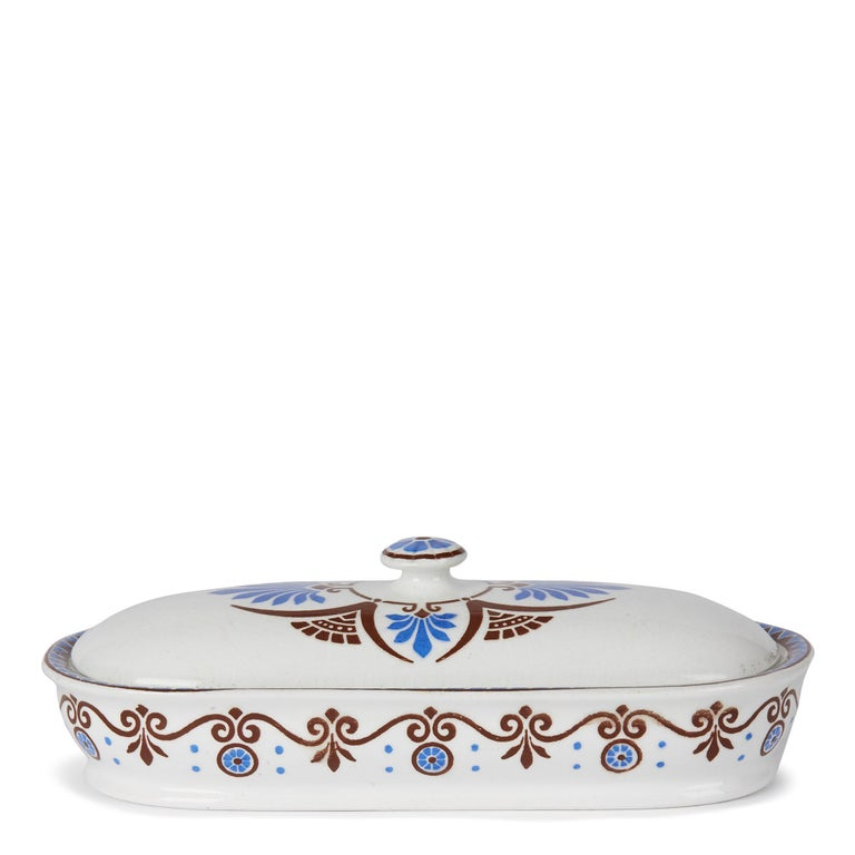 A stylish aesthetic movement Minton pottery bathroom or razor lidded box decorated with a printed design by Christopher Dresser. The long oval ended box has a central domed cover and is decorated in brown and blue printed patterns. The box has