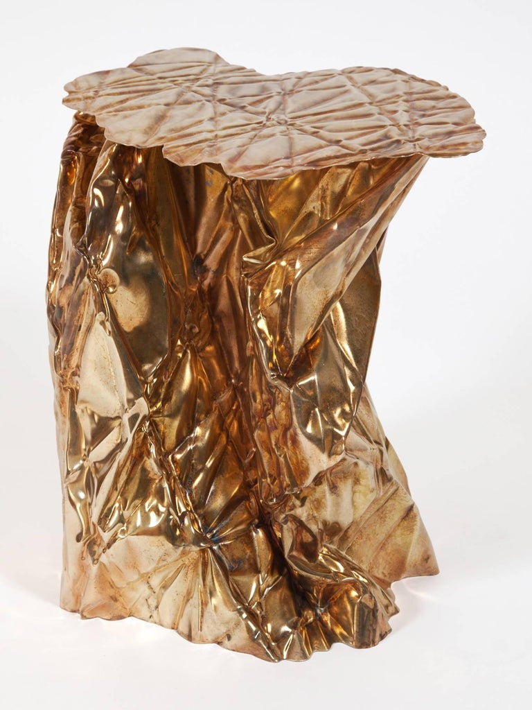 Wrinkled steel side table by Omaha-based designer Cristopher Prinz. Available in copper, yellow zinc, iridescent zinc nickel, zinc nickel, brass, or black oxide finishes (shown here in brass). Made to order with a lead time of 8-10 weeks; custom