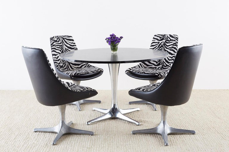 Iconic Mid-Century Modern dining table featuring a large tulip-formed polished aluminium column base. Mady by Chromcraft from their decorables collection circa 1968. Large round laminate top with a black formica surface. The table is supported by a