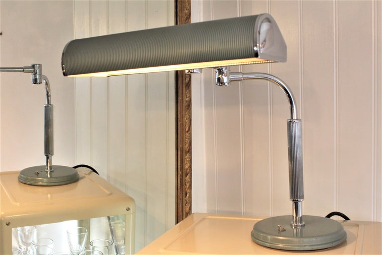 Chrome-plated with green lacquered metal shade desk lamp. This is a heavy and quality lamp, hence why there is little pitting after all these years. Fully articulated, the two arms can be adjusted and pivoted. The shade too rotates.  It is a really