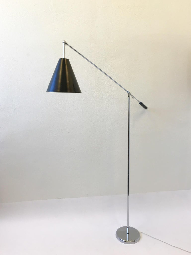 A beautiful polish chrome and black lacquered adjustable floor lamp by Robert Sonneman. The lamp has been newly rewired, but the chrome and the lacquered is in original condition. The lamp shows some minor wear. The arm can be adjusted up and down