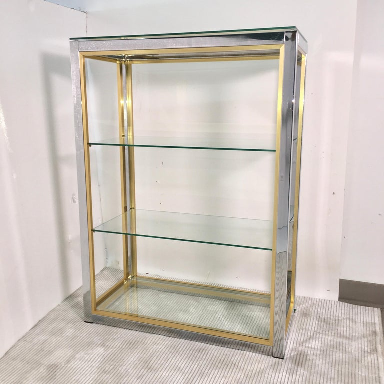 This is a chromed steel and brass trim small scale étagère, in the round, open from all sides, with four removable tempered safety glass shelves; two center, one floating on top and one bottom glass shelf inset within the floor.