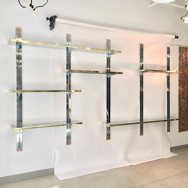 Blingy and glamorous 1970s custom made wall mounted shelves consisting of chromed steel single-track shelf standard which is embedded within a channel of a 75 inch length of 3 inch laminated wood which has been clad in mirror polished stainless