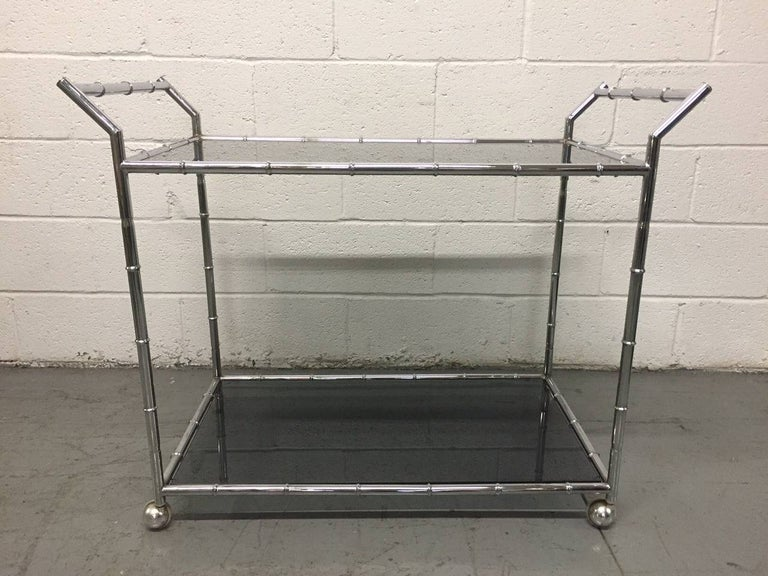 Two-tier bar or serving cart, smoked glass tops with a chrome faux bamboo frame.