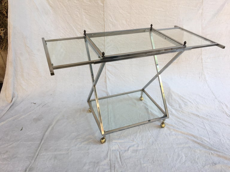 1970s chrome and glass bar cart with brass finales at each corner. Glass leafs pull out from each end to allow for ample work space. Each leaf is a little over 12