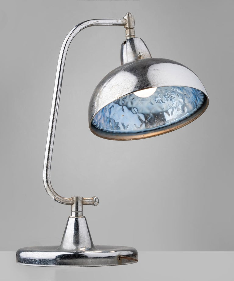 Chrome table lamp with blue glass interior,America circa 1950.  Chrome plated brass table lamp with interior blue glass reflector. Manufactured by Apollo Electric Co.. Crack on interior shade noted in pictures.